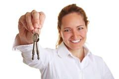 Bedrijfs vrouw die twee sleutels houdt Stock Fotografie