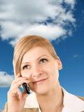 Bedrijfs vrouw met celtelefoon op de hemelachtergrond Stock Foto's