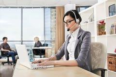 Bedrijfs vrouw met hoofdtelefoon in een bureau Royalty-vrije Stock Fotografie