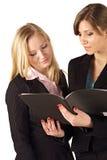 Bedrijfs vrouwen die een dossier controleren Royalty-vrije Stock Afbeeldingen