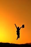 Bedrijfs vrouwen het springen en van de zonsondergang silhouet Royalty-vrije Stock Foto