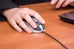 Bedrijfs vrouwenhand die aan een computermuis werkt bij Stock Afbeeldingen