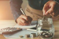 bedrijfsaccountin met besparingsgeld met hand die muntstukken aanbrengen stock afbeeldingen