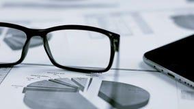 Bedrijfsachtergrond met grafiek en glazen stock footage