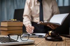 Bedrijfsadvocaat die hard bij bureauwerkplaats werken met boek stock foto