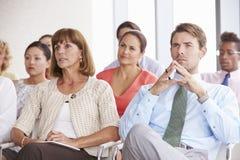 Bedrijfsafgevaardigden die aan Presentatie op Conferentie luisteren Stock Foto's