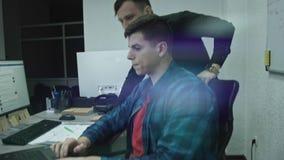 Bedrijfsarbeiders in bespreking bij computer in bureau stock videobeelden