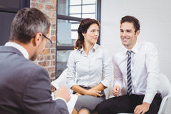 Bedrijfsberoeps die met glimlachende cliënten bespreken stock foto