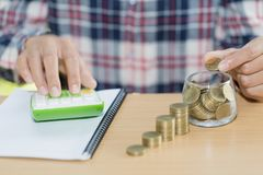bedrijfsboekhouding met besparingsgeld met hand die muntstukken aanbrengen royalty-vrije stock afbeeldingen