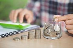 Bedrijfsboekhouding met besparingsgeld met hand die muntstukken in kruikglas zetten, Zakenman Writing Financial Accounting, conce royalty-vrije stock afbeelding
