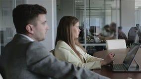 bedrijfsbureauconcept De partners onderhandelen bij de lijst in het bureau stock footage