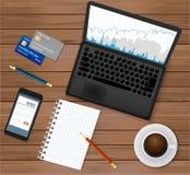 Bedrijfsbureauwerkplaats Hoogste mening Laptop met financiële grafiek op het scherm, koffiekop, smartphone, creditcards, blocnote Royalty-vrije Stock Afbeeldingen