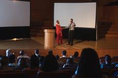 Bedrijfscollega die en zich met elkaar voor het publiek in auditorium bevinden bespreken royalty-vrije stock foto's