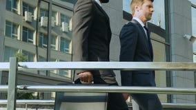 Bedrijfscollega's die de bureaubouw verlaten, die het werkdag, beroeps bespreken stock video