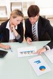 Bedrijfscollega's die een grafiek bespreken Stock Afbeeldingen