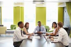 Bedrijfscollega's die een informele vergadering hebben op het werk stock afbeeldingen