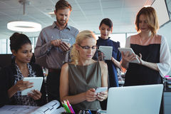 Bedrijfscollega's die mobiele telefoons en digitale tabletten samen gebruiken stock afbeelding