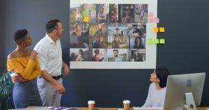 Bedrijfscollega's die over foto's in de vergadering 4k bespreken stock video