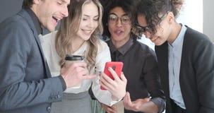 Bedrijfscollega's die pret het letten op media inhoud op mobiele telefoon hebben stock video