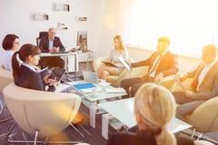 Bedrijfscollega's die tijdens Vergadering in Bureau bespreken stock afbeeldingen