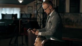 Bedrijfscollega's in pakken Één van hen drinkt whisky, en de tweede bekijkt de telefoon en controleert e-mail of stock videobeelden