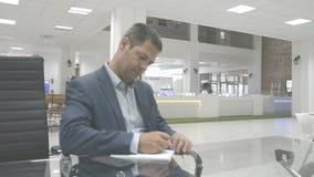 Bedrijfsconcept: Mens in de bureauwerkplaats die in de nota schrijven stock footage