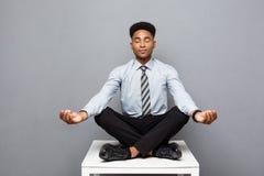 Bedrijfsconcept - portret van Afrikaanse Amerikaanse zakenman die meditatie en yoga doen binnen alvorens te werken royalty-vrije stock afbeeldingen