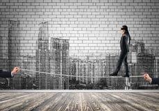 Bedrijfsconcept risicosteun en hulp met mens het in evenwicht brengen op kabel stock afbeelding