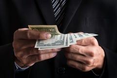 bedrijfsconcept, stapel van het Zakenman de tellende geld dollars binnen stock fotografie