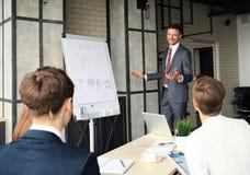 Bedrijfsconferentiepresentatie met team opleidings flipchart bureau stock afbeelding