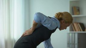 Bedrijfsdame die lagere rugpijn, zenuwontsteking, sedentair het levensresultaat voelen stock footage