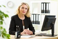 bedrijfsdame die op middelbare leeftijd in bureau werken royalty-vrije stock afbeelding