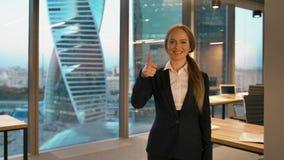 Bedrijfsdame in het formele speels stellen op camera die als teken met omhoog duim geven stock video