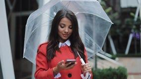 Bedrijfsdame in rode laag die audioingesproken bericht op smartphone verzenden bij het openlucht spreken naar mobiele medewerker  stock videobeelden