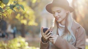 Bedrijfsdame in zwarte hoed die audioingesproken bericht op cellphone verzenden bij het openlucht spreken naar mobiele medewerker stock videobeelden