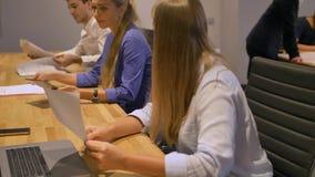 Bedrijfsdames en zijn mannelijke collega's op vergadering in de moderne binnenlandse brainstorming van het nachtbureau stock video