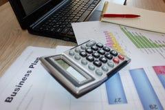 Bedrijfsdesktop met laptop, calculator en financiële verslagen, hoogste mening Stock Afbeelding