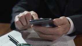 Bedrijfsdeskundige die financieel nieuwsvoer op smartphone scrollen, die aan contract werken stock videobeelden