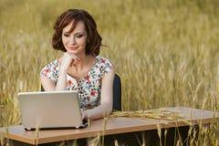 Bedrijfsdieconcept van een mooie jonge vrouwenzitting bij een bureau wordt geschoten die een computer op een gebied met behulp va Stock Foto's
