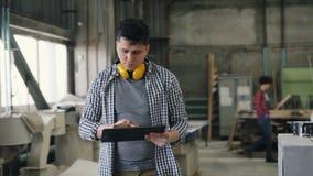 Bedrijfseigenaarmens die in houten workshop met laptop lopen die inventaris doen stock videobeelden