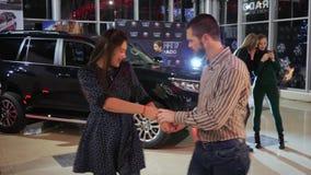 Bedrijfsgebeurtenis, gelukkig paar die in het centrum van de autoverkoop dichtbij nieuwe auto dansen bij nacht stock videobeelden