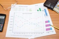 Bedrijfsgrafieken met geld, calculator, glazen en pen Stock Foto's