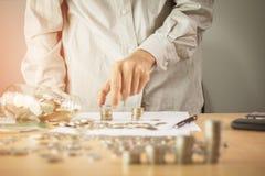 Bedrijfshand die een pen op de lijst met een medaille houden die berekening en Zonsondergang lichte Bedrijfsachtergrond erkennen royalty-vrije stock foto's