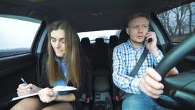 Bedrijfskerel en meisje in de auto, de kerel die de telefoon werken stock video