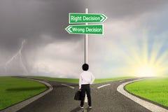 Bedrijfskind met een teken van recht versus verkeerd besluit Stock Afbeeldingen