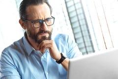 Bedrijfslevensstijl Handelaar die in glazen bij koffie controlevoorraden zitten op laptop geconcentreerd close-up royalty-vrije stock foto