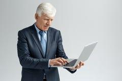 Bedrijfslevensstijl Zakenman status geïsoleerd op grijs het doorbladeren geconcentreerd Web op laptop royalty-vrije stock foto