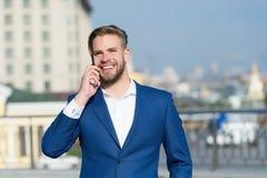 Bedrijfslevensstijlconcept Gelukkige zakenman met smartphone op zonnig terras Mensenglimlach in formeel kostuum met mobiele telef stock afbeeldingen