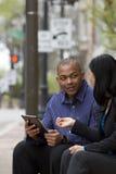 Bedrijfsman en vrouw buiten op hun onderbreking met hun tabletten stock afbeeldingen