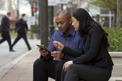 Bedrijfsman en vrouw buiten op hun onderbreking met hun tabletten stock foto